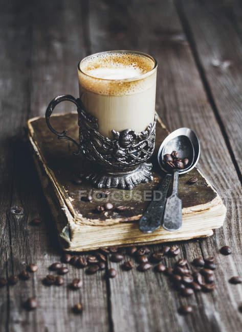 White coffee in retro glass on book with coffee beans — Stock Photo