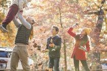 Padre giocoso e bambini che giocano in foglie autunnali — Foto stock