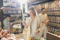 Young woman using cell phone, grocery shopping in market — Stock Photo