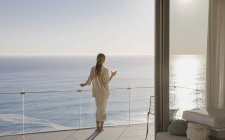 Woman standing on sunny luxury balcony with ocean view — Stock Photo