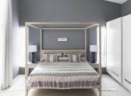 Roupa de cama listrada na cama de dossel no quarto interior moderna casa vitrine — Fotografia de Stock