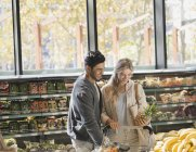 Smiling young couple grocery shopping, holding pineapple in market — Stock Photo
