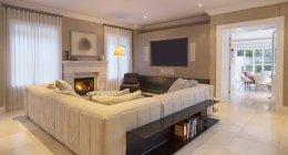 Vitrine casa sala de estar com lareira e sofá secional — Fotografia de Stock