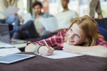 Femme par écrit au bureau en position couchée sur la table — Photo de stock