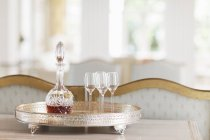 Crystal sherry decanter and cordial glasses on silver tray — Stock Photo