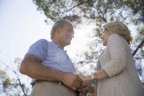 Heureux couple aîné tenant la main sous l'arbre — Photo de stock