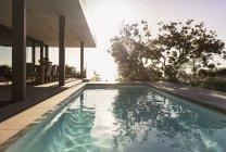 Reflet de l'arbre dans la piscine sous-abdominale à l'extérieur de la vitrine de luxe moderne — Photo de stock