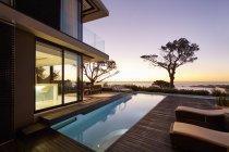 Moderna casa di lusso vetrina patio e piscina con vista sull'oceano tramonto — Foto stock