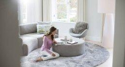 Женщина читает журнал на оттоманском в гостиной — стоковое фото
