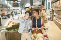Smiling young lesbian couple taking selfie in grocery store market — Stock Photo