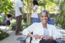 Portrait of smiling senior woman on patio with family in background — Stock Photo