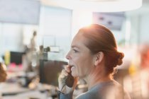 Profile businesswoman talking on telephone in office — Stock Photo