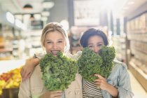 Portrait playful young lesbian couple holding fresh kale in grocery store market — Stock Photo