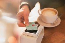 Man zahlt für Cappuccino mit kontaktlose Kreditkartenzahlung im Café hautnah — Stockfoto