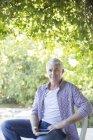 Homem mais velho sentado com tablet digital ao ar livre — Fotografia de Stock