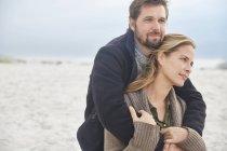 Serene affectionate couple hugging on winter beach — Stock Photo