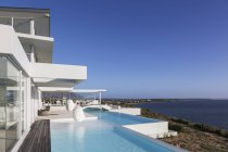 Sunny, tranquil modern luxury home showcase exterior with infinity pool and ocean view under blue sky — Stock Photo