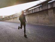 Male runner running on urban street into tunnel — Stock Photo
