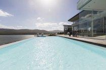 Sunny tranquilla casa di lusso moderna vetrina esterna con piscina a sfioro e vista sull'oceano — Foto stock