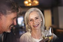 Portrait smiling senior couple drinking white wine in bar — Stock Photo