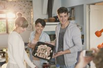 Young friends roommates cooking posing for friend using camera phone — Stock Photo