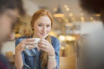 Happy young friends enjoying coffee in cafe — Stock Photo