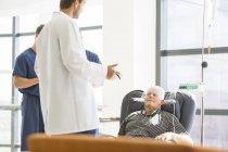 Deux médecins parlant à haut patient subissant un traitement médical en clinique externe — Photo de stock