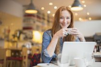 Happy young woman using laptop in cafe — Stock Photo