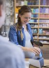 Беременная женщина с помощью кредитных карт читателя в магазине — стоковое фото