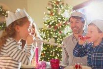 Família usando coroas de papel na mesa de jantar de Natal — Fotografia de Stock