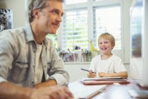 Father and son working in home office — Stock Photo
