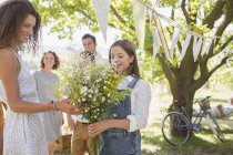 Woman admiring flowers held by young girl — Stock Photo