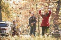 Meninos e menina jogando folhas de outono sobrecarga — Fotografia de Stock