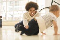 Madre guardare bambino ragazzo strisciare sul pavimento del soggiorno a casa — Foto stock