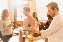 Бармен наливает пиво в пивной кран за баром — стоковое фото