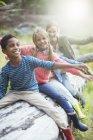 Schüler und Lehrer sitzen auf melden Sie sich im Wald — Stockfoto