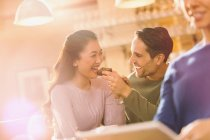 Playful boyfriend feeding brownie to girlfriend at cafe — Stock Photo