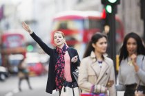 Woman signaling for taxi on city street — Stock Photo
