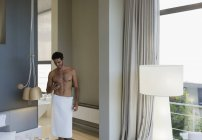 Man in towel texting with cell phone in bedroom — Stock Photo