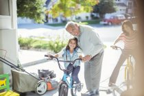 Grandfather and granddaughter on bike in garage — Stock Photo