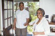 Portrait of smiling senior couple holding hands in doorway — Stock Photo