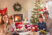 Portrait souriant jeune famille portant des bois de renne de costume à la table de dîner de Noël — Photo de stock