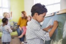 Student drawing on chalkboard in classroom — Stock Photo