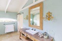Lavabo y espejo en baño rusticos - foto de stock