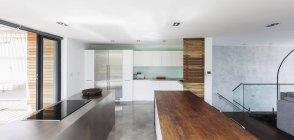 Cozinha interior de vitrine casa moderna e minimalista com balcões de madeira e aço inoxidável — Fotografia de Stock