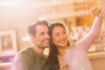 Lächelnde paar Gestikulieren Friedenszeichen nehmen Selfie mit Kamera-Handy — Stockfoto