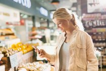 Young woman using cell phone in grocery store market — Stock Photo