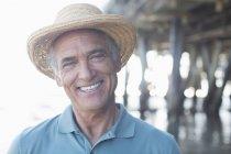 Portrait de sourire senior homme au chapeau de soleil à la plage — Photo de stock