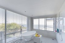 Modern luxury home showcase interior bathroom with soaking tub and ocean view — Stock Photo