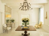 Chandelier over rose bouquet on table in luxury foyer — Stock Photo